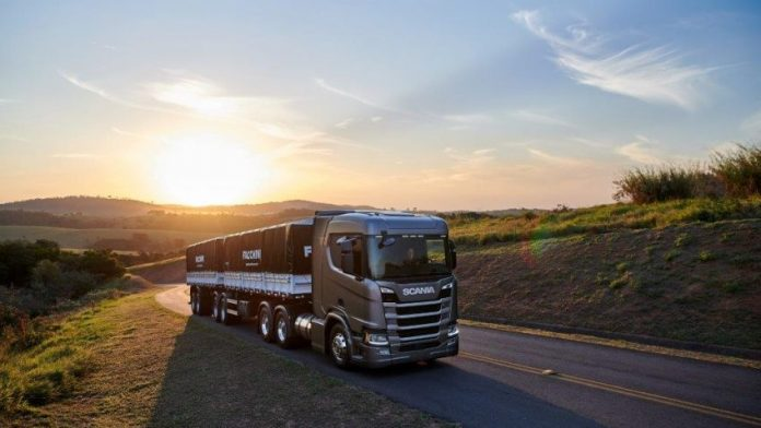 Em dia de céu claro e por do sol, caminhão cinza com carga preta anda em estrada
