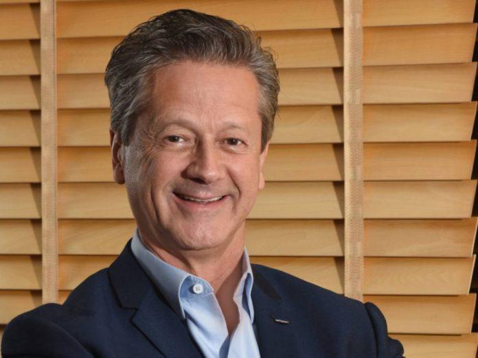 Alarico Assumpção Júnior, Presidente da FENABRAVE, posa para foto. Homem branco, veste camisa social azul claro e terno preto diante de fundo neutro de persiana de tom marrom claro.