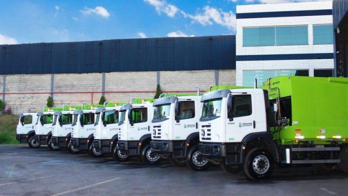 fila de caminhões de cabine branca e carroceria verde-claro estacionados em pátio