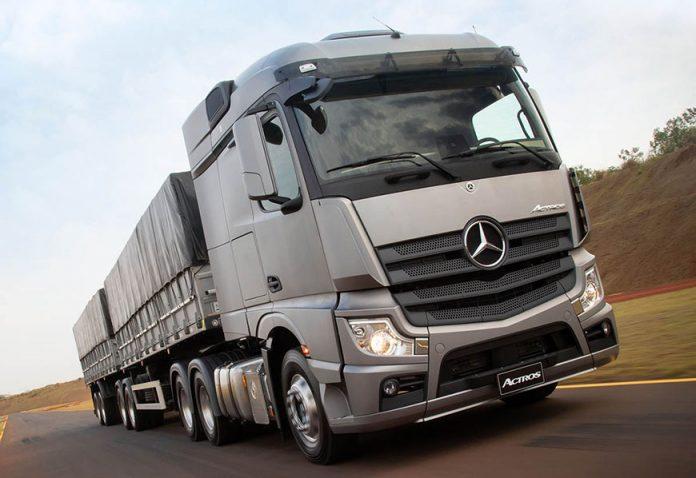 Caminhão prateado da Mercedes-Benz leva carga em estrada em dia de céu claro