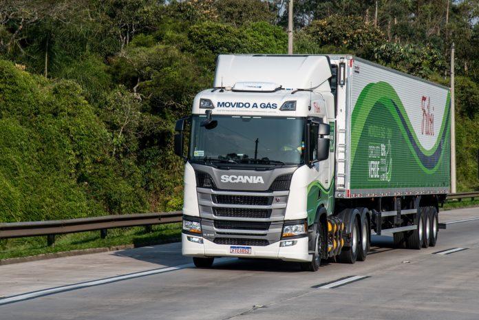 Caminhão a gás da Scania de cor branca e carroceria branca e verde em estrada, com árvores verdes ao fundo